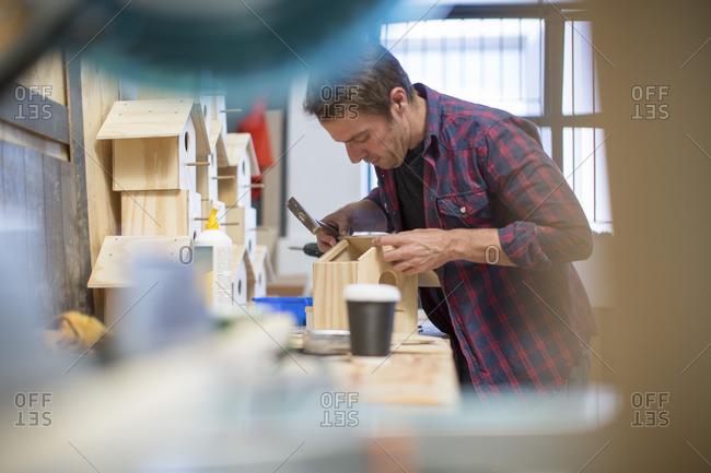 Man working on birdhouse in workshop