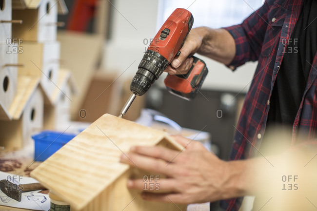 Man working with electric drill on birdhouse in workshop
