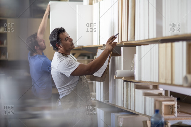 Man counting stock in canvas workshop