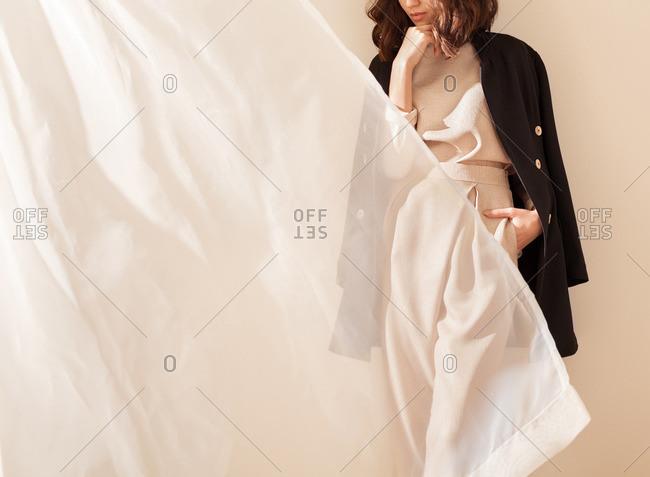 Woman standing near a curtain wearing stylish clothing