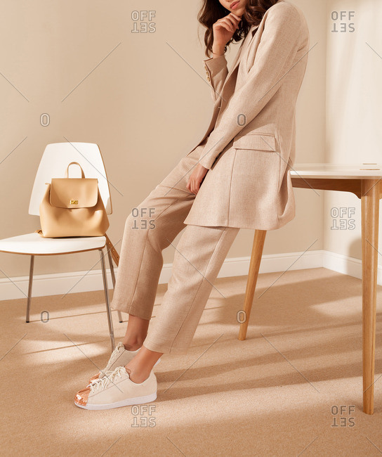Woman leaning against a table wearing stylish clothing