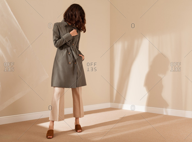 Woman in an empty room wearing stylish clothing