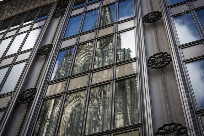 A cathedral reflected in the windows of a building in Cologne, Germany