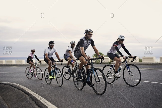 Group of cyclists riding up a steep hill together