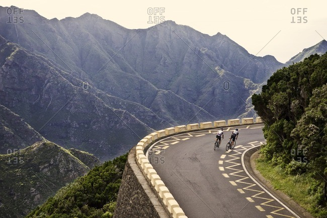 A pair of cyclists riding up a steep hill together