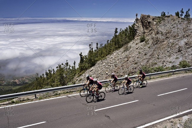 Group of cyclists riding along a scenic mountain road