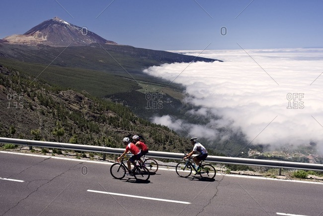 Small group of cyclists riding along a mountain road