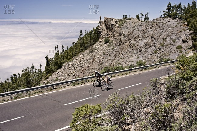Pair of cyclists riding along a mountain road
