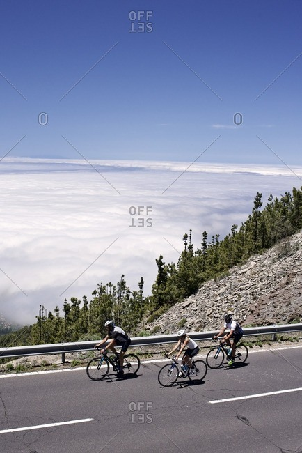 Three cyclists riding along a mountain road