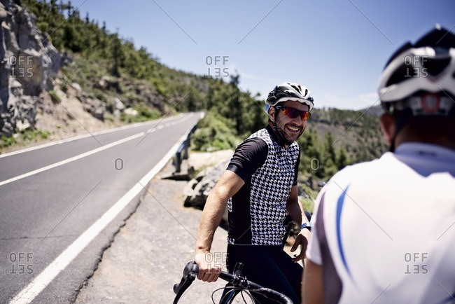 Two cyclists taking a break along a scenic mountain overlook