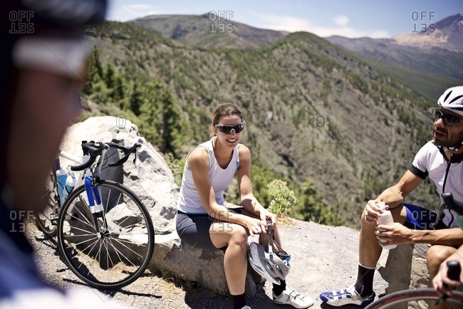 Several cyclists taking a break along a scenic mountain overlook