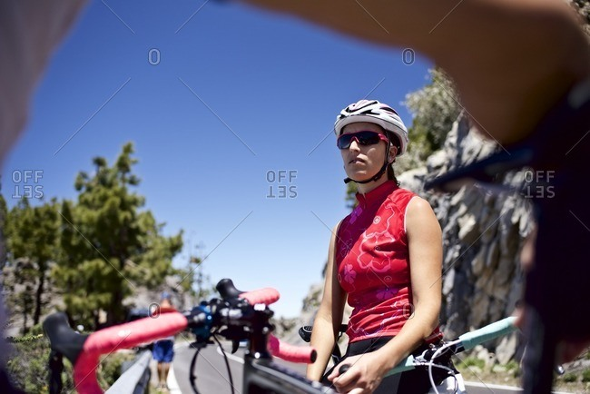 Female cyclist taking a break along a scenic mountain overlook