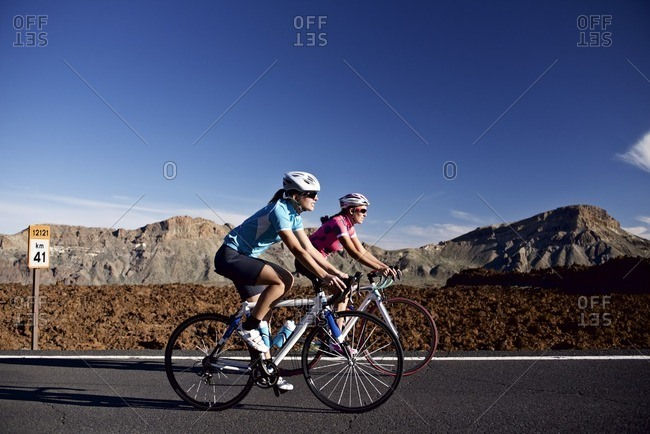 A pair of cyclists riding along a rural road together