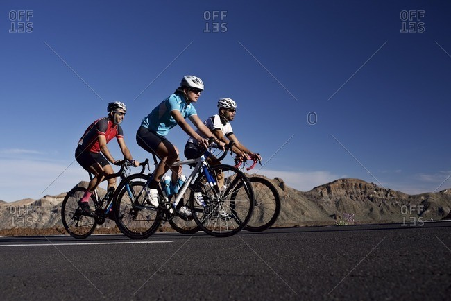 Three cyclists riding along a rural mountain road together