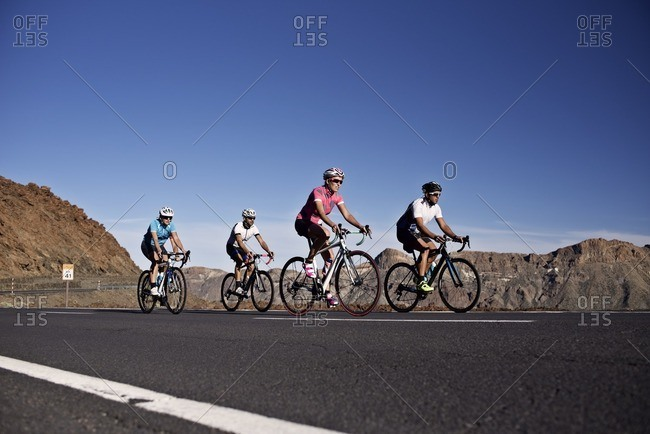 Cyclists riding along a rural mountain road together