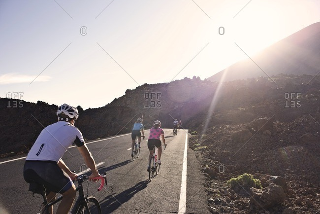 Cyclists riding along a rural mountain road