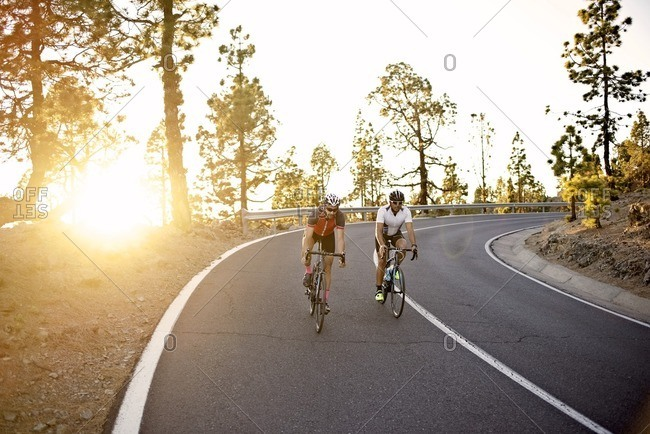 A pair of cyclists descending a rural mountain road together