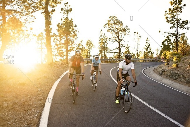 Three cyclists descending a rural mountain road together