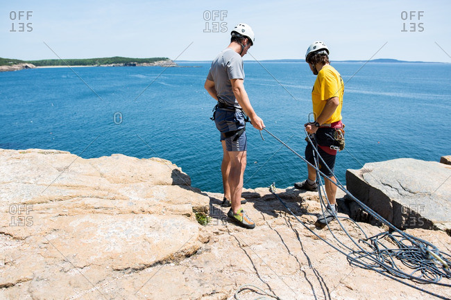 Male rock climbers on coastal cliff