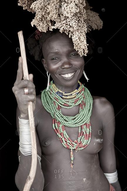 Omo Valley, Ethiopia - January 26, 2009: Dassenech woman with sorghum on head, Omo Valley, Ethiopia