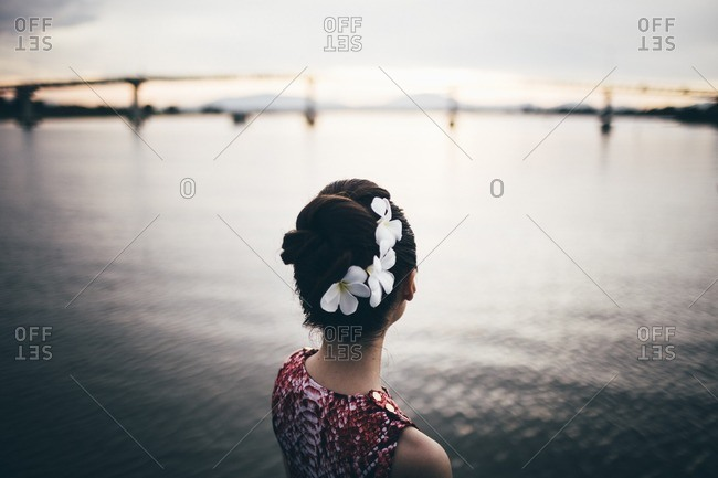 A young Asian woman overlooks a river in central Vietnam at sunset