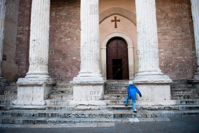 Boy walking up to Temple of Minerva in Assisi, Italy