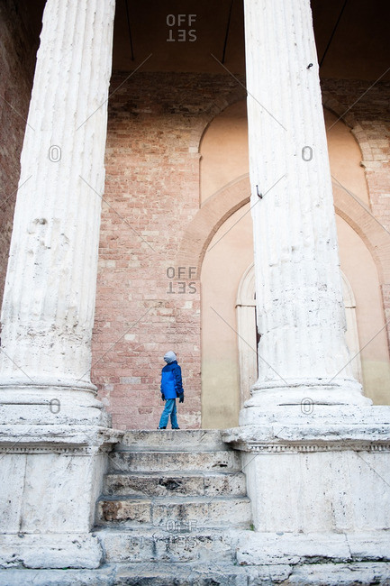 Young boy looking up at Temple of Minerva in Assisi, Italy