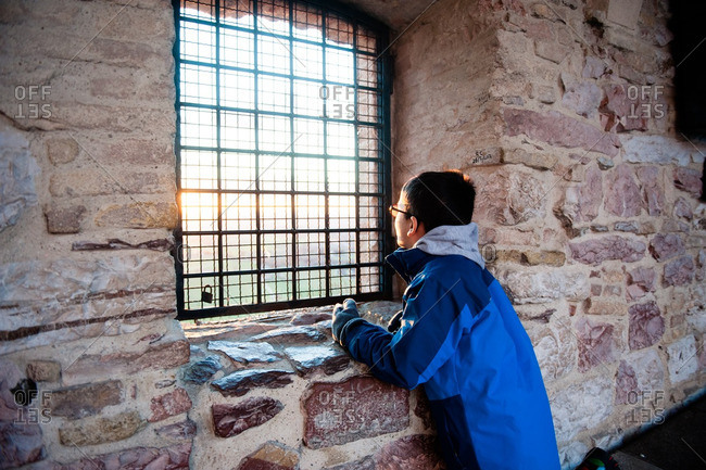 Boy looking out window of stone building
