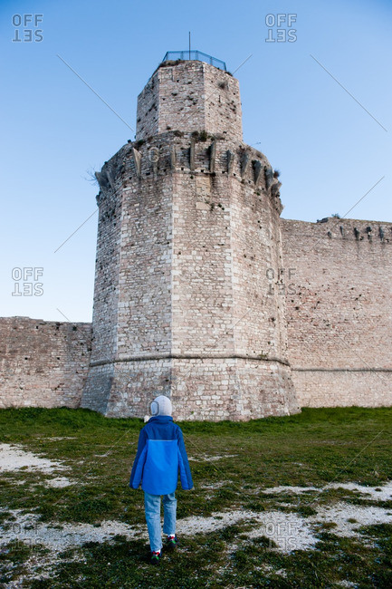 Boy standing outside fortress wall