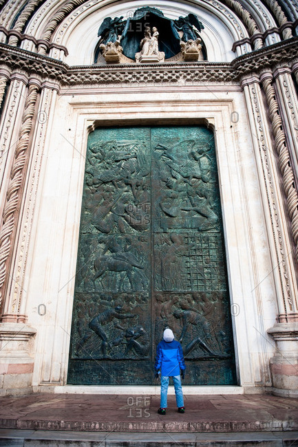 Boy looking up at bronze door of Duomo of Orvieto, Italy