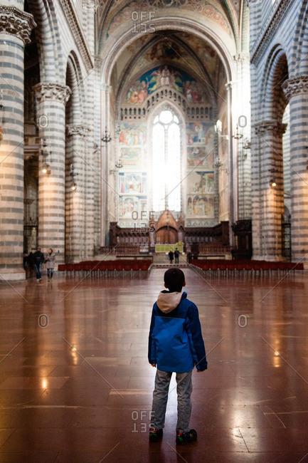 Orvieto, Italy - January 17, 2016: Boy looking towards front of Orvieto Cathedral
