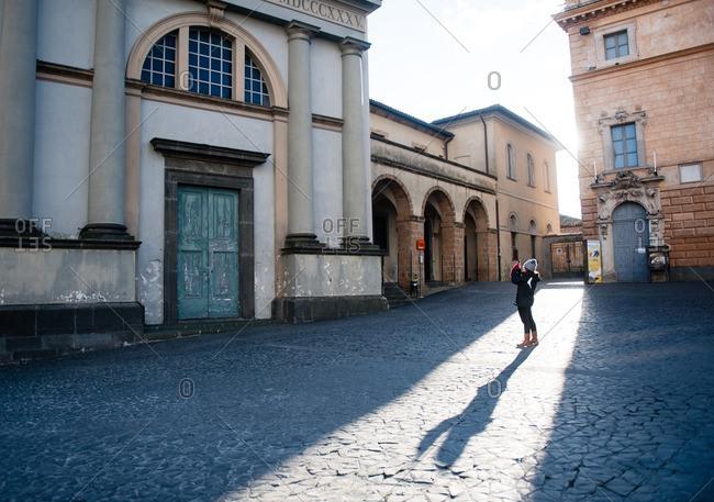 Orvieto, Italy - January 17, 2016: Girl taking a photo of building in Orvieto