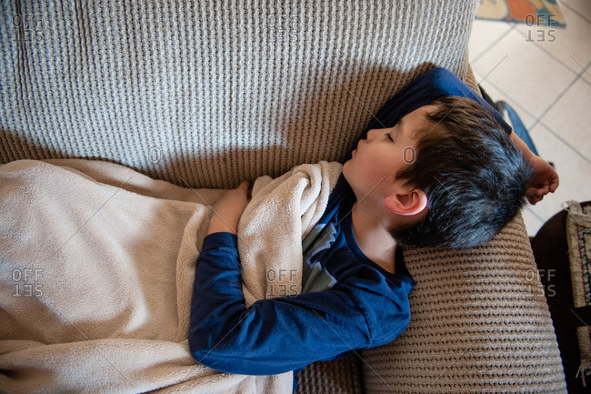 Young boy sleeping under a blanket on couch