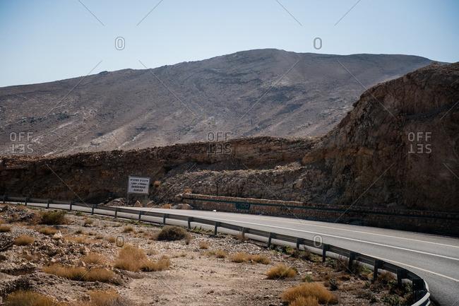 Warning sign on road in desert, Israel