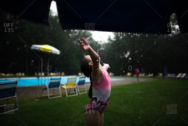 Girl standing outside near a swimming pool during a rain storm