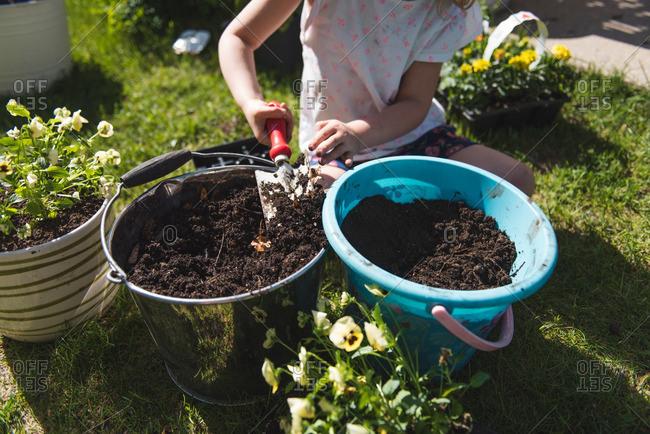 Child digging in pails of potting soil