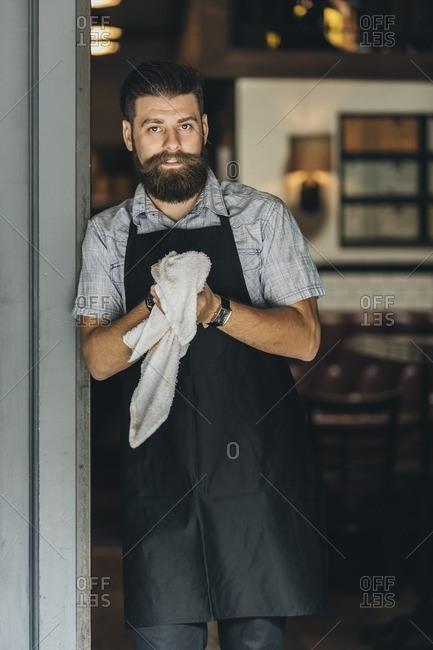 Bartender standing in doorway to bar holding towel