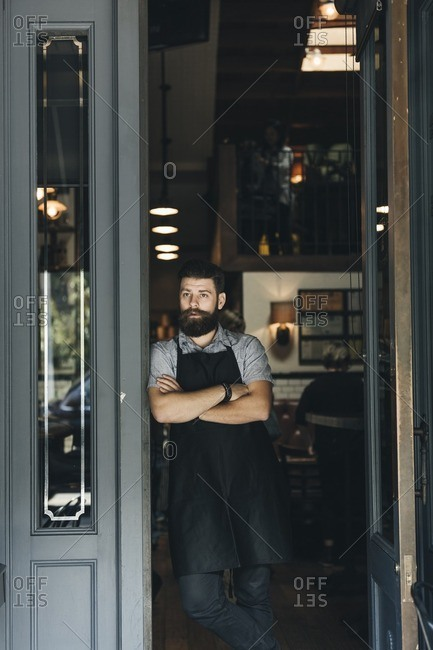 Bartender standing in doorway to bar with arms crossed