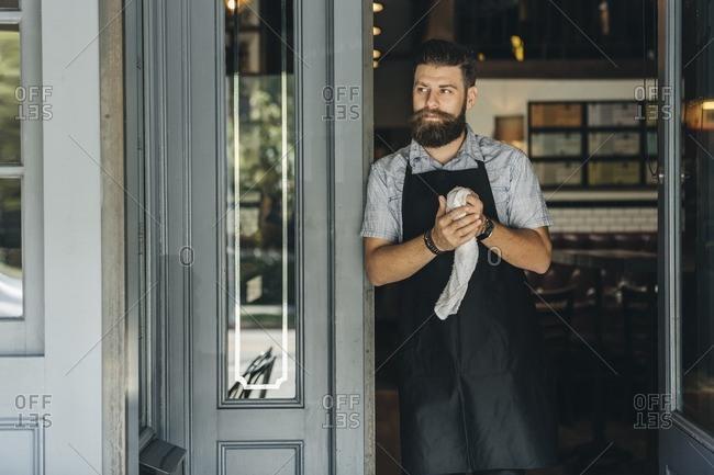 Bartender standing in doorway to bar holding a wet rag