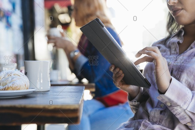 Woman using tablet while having coffee at an outdoor cafe