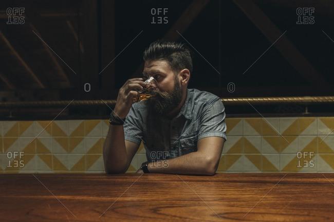 Man drinking straight liquor at a bar