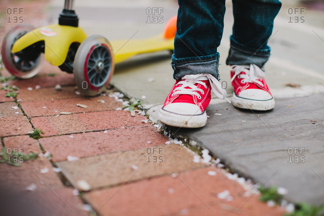 Red sneakers on feet of child with scooter