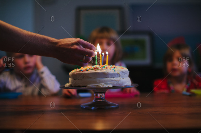 Children watch as adult light candles on a birthday cake