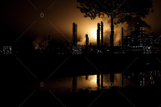 Silhouette of factory with smoke at night