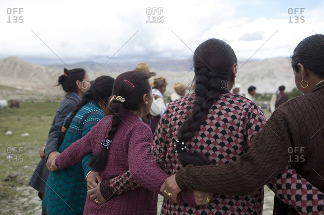 Women standing with arms around one another in Lo Manthang, Mustang, Nepal