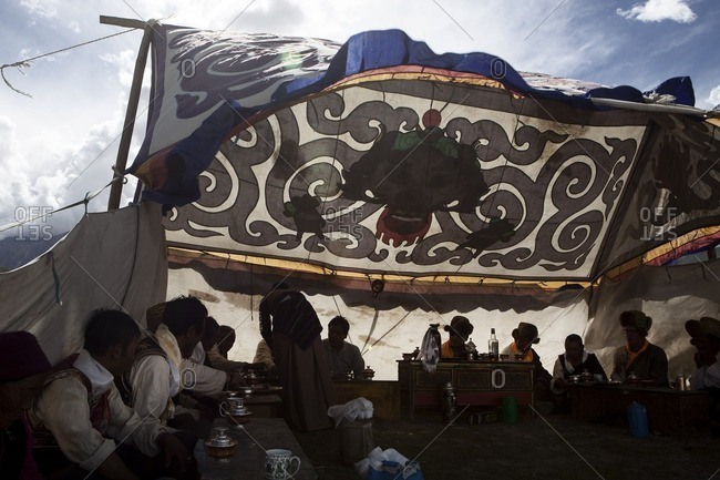 Lo Manthang, Mustang, Nepal - August 20, 2015: Villagers sit and drink inside of a tent set up in the open grass fields during the Yartung celebration