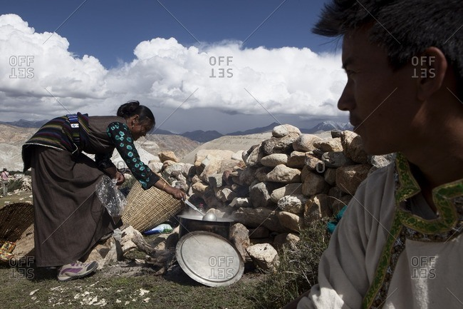 Lo Manthang, Mustang, Nepal - August 20, 2015: A women prepares Yak butter tea in an open field during the Yartung Festival