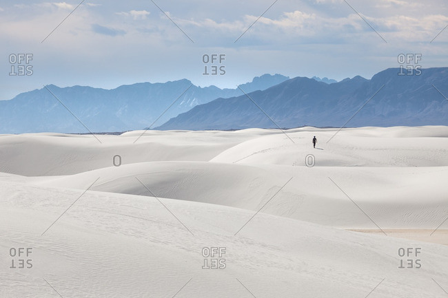 Man walking on a sand dune towards San Andres Mountains at White Sands National Monument