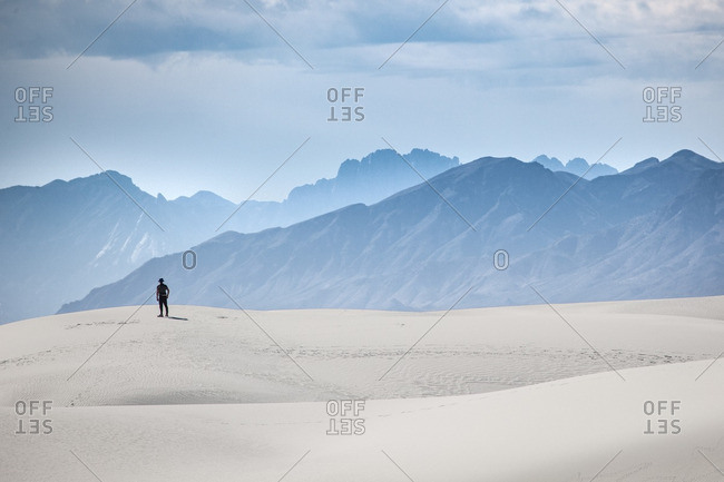 Man standing on a sand dune towards San Andres Mountains at White Sands National Monument