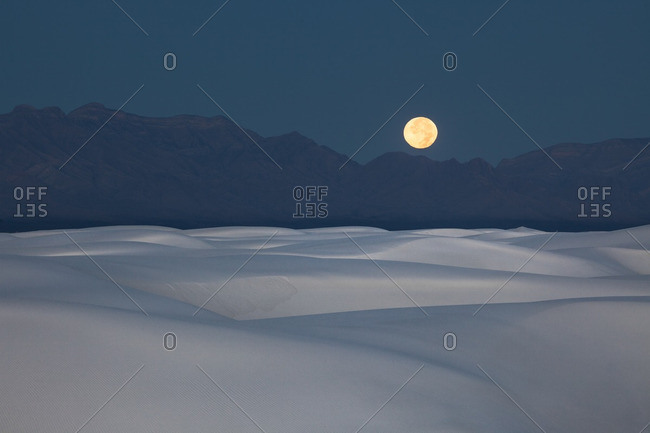 Full moon setting at dawn over San Andres Mountains near White Sands National Monument